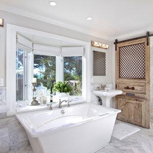 Modelo de cuarto de baño principal, tradicional, grande, con bañera exenta, baldosas y/o azulejos grises, baldosas y/o azulejos de mármol, paredes blancas, suelo de mármol, lavabo con pedestal, suelo blanco, ducha con puerta corredera y encimeras amarillas