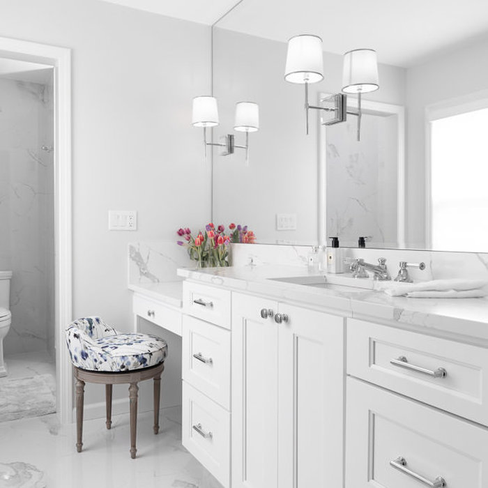 The master vanity of Engineered Quartz is elegant and durable, large enough to display personal items and still drops down to a seated vanity. Visual Comfort Wall Sconces on the full mirror accentual