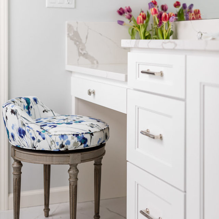 """The master bathroom seated vanity is highlighted by custom upholstery with a delightful pop of color. The 4"""" backsplash that runs along the main bath vanity continues to an 8"""" height at the seated van"""