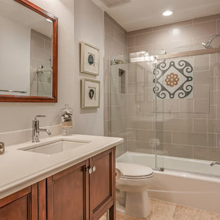 Mid-sized tuscan 3/4 gray tile and subway tile beige floor bathroom photo in Houston with beaded inset cabinets, medium tone wood cabinets, white walls, an undermount sink, a two-piece toilet and solid surface countertops