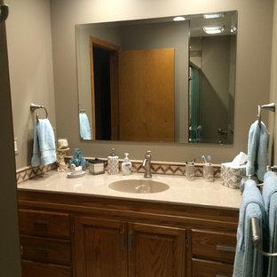 Diseño de cuarto de baño con ducha, clásico, de tamaño medio, con lavabo integrado, armarios con paneles con relieve, puertas de armario de madera oscura, encimera de ónix, baldosas y/o azulejos marrones, baldosas y/o azulejos de porcelana, paredes beige y suelo vinílico