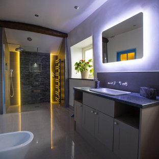 Inspiration for a large classic shower room bathroom in Other with shaker cabinets, grey cabinets, a walk-in shower, a wall mounted toilet, grey tiles, grey walls, a built-in sink, grey floors, an open shower, black worktops, a wall niche, a single sink and a built in vanity unit.