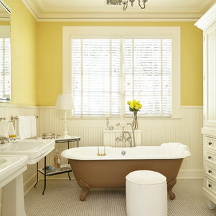 Example of a classic mosaic tile floor claw-foot bathtub design in Atlanta with white cabinets, yellow walls, a pedestal sink and recessed-panel cabinets
