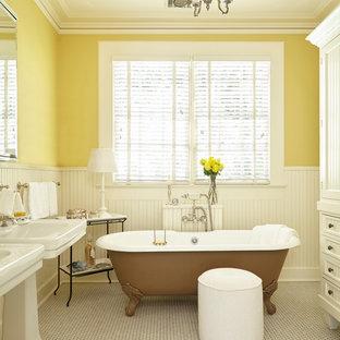 Immagine di una stanza da bagno chic con ante bianche, pareti gialle, pavimento con piastrelle a mosaico, lavabo a colonna, ante con riquadro incassato e vasca con piedi a zampa di leone
