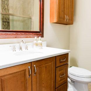 シアトルの中サイズのトラディショナルスタイルのおしゃれな浴室 (レイズドパネル扉のキャビネット、中間色木目調キャビネット、アルコーブ型シャワー、分離型トイレ、マルチカラーのタイル、磁器タイル、ベージュの壁、竹フローリング、アンダーカウンター洗面器、クオーツストーンの洗面台、茶色い床、引戸のシャワー) の写真