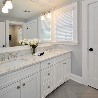 Esempio di una grande stanza da bagno padronale design con vasca sottopiano, ante con riquadro incassato, ante bianche, pareti grigie, parquet chiaro, lavabo sottopiano, top in marmo e pavimento marrone