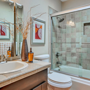Mid-sized southwest 3/4 multicolored tile and ceramic tile bathroom photo in Austin with dark wood cabinets, beige walls, a drop-in sink, tile countertops and beige countertops