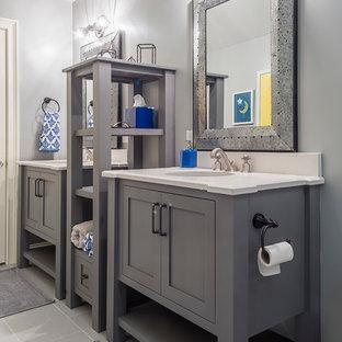 Idéer för att renovera ett mellanstort eklektiskt badrum för barn, med möbel-liknande, grå skåp, en dusch i en alkov, en toalettstol med separat cisternkåpa, grå kakel, porslinskakel, grå väggar, klinkergolv i porslin, ett undermonterad handfat och bänkskiva i kvarts