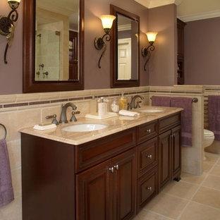 Esempio di una stanza da bagno tradizionale con lavabo sottopiano, ante con bugna sagomata, ante in legno bruno e piastrelle beige