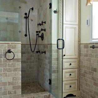 Exempel på ett litet medelhavsstil en-suite badrum, med ett undermonterad handfat, vita skåp, en dusch i en alkov, beige kakel, beige väggar, travertin golv, luckor med infälld panel och travertinkakel