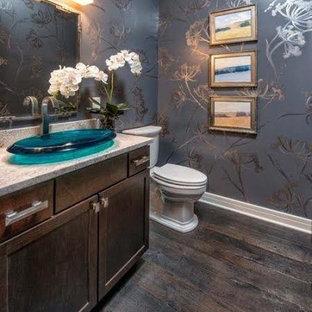 Modelo de cuarto de baño con ducha, minimalista, con armarios con paneles lisos, puertas de armario marrones, sanitario de dos piezas, paredes grises, suelo de madera oscura, lavabo sobreencimera y encimera de granito