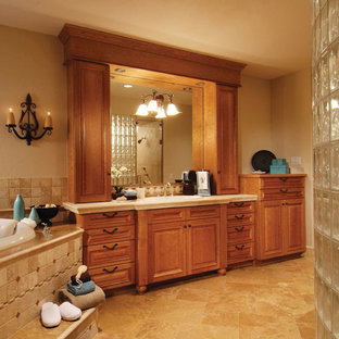 Example of a classic master beige tile and ceramic tile travertine floor corner bathtub design in Denver with raised-panel cabinets, medium tone wood cabinets, beige walls, a drop-in sink and solid surface countertops