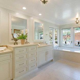 Idéer för att renovera ett stort vintage beige beige en-suite badrum, med luckor med infälld panel, beige skåp, ett undermonterat badkar, en dusch i en alkov, en toalettstol med separat cisternkåpa, beige kakel, porslinskakel, gröna väggar, klinkergolv i porslin, ett undermonterad handfat, bänkskiva i kvarts, beiget golv och dusch med gångjärnsdörr