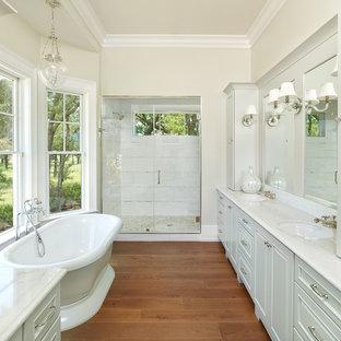 Стильный дизайн: главная ванная комната среднего размера в классическом стиле с отдельно стоящей ванной, паркетным полом среднего тона, мраморной столешницей, душем в нише, бежевыми стенами, врезной раковиной, душем с распашными дверями, фасадами с декоративным кантом, серыми фасадами, белой плиткой, мраморной плиткой, коричневым полом и белой столешницей - последний тренд