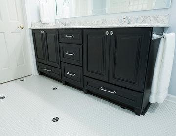 Traditional master bathroom with dark wood vanity & penny tile floor