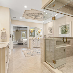 Inspiration for a huge timeless master light wood floor and beige floor bathroom remodel in Cleveland with recessed-panel cabinets, beige cabinets, beige walls, an undermount sink, marble countertops, a hinged shower door and beige countertops