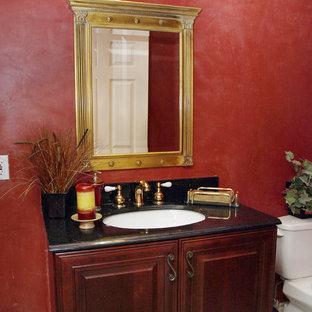 Esempio di una stanza da bagno tradizionale di medie dimensioni con ante con bugna sagomata, ante in legno bruno, WC a due pezzi, piastrelle nere, pareti rosse, lavabo sottopiano, piastrelle di marmo, pavimento in marmo e top in granito