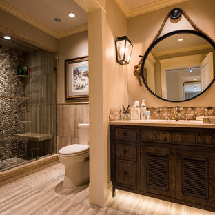 Photo of a medium sized rustic shower room in New York with beaded cabinets, dark wood cabinets, an alcove shower, a two-piece toilet, beige tiles, pebble tiles, beige walls, ceramic flooring, a submerged sink and granite worktops.