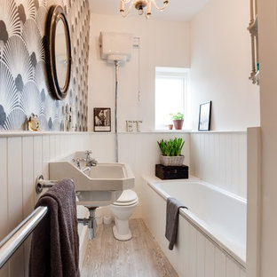 Small victorian bathroom in Hampshire with a wall-mounted sink, a built-in bath, a two-piece toilet, multi-coloured walls and light hardwood flooring.