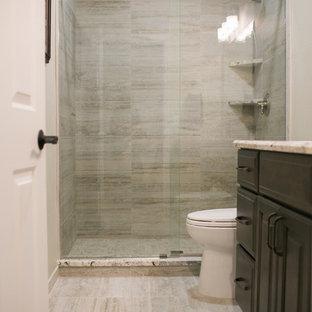 Foto de cuarto de baño con ducha, clásico, pequeño, con armarios con paneles con relieve, puertas de armario de madera en tonos medios, ducha a ras de suelo, sanitario de dos piezas, baldosas y/o azulejos grises, baldosas y/o azulejos de porcelana, paredes grises, suelo de baldosas de porcelana, lavabo bajoencimera y encimera de granito