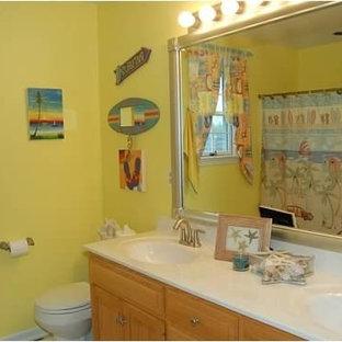 Immagine di una stanza da bagno per bambini costiera di medie dimensioni con ante con bugna sagomata, ante in legno chiaro, vasca ad alcova, WC a due pezzi, pareti gialle, pavimento in vinile, lavabo integrato e top in superficie solida