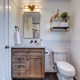 Modelo de cuarto de baño infantil, de estilo de casa de campo, pequeño, con armarios estilo shaker, puertas de armario de madera oscura, bañera empotrada, combinación de ducha y bañera, sanitario de dos piezas, baldosas y/o azulejos blancos, baldosas y/o azulejos de porcelana, paredes blancas, suelo de baldosas de porcelana, lavabo encastrado, encimera de cuarzo compacto, suelo negro, ducha con cortina y encimeras blancas