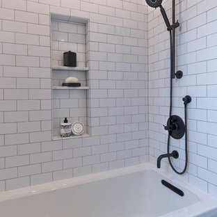 Photo of a small country family bathroom in San Francisco with shaker cabinets, medium wood cabinets, an alcove bath, a shower/bath combination, a two-piece toilet, porcelain tiles, white walls, porcelain flooring, a built-in sink, engineered stone worktops, black floors, a shower curtain, white worktops and white tiles.