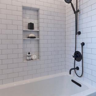 サンフランシスコの小さいカントリー風おしゃれな子供用バスルーム (シェーカースタイル扉のキャビネット、中間色木目調キャビネット、アルコーブ型浴槽、シャワー付き浴槽、分離型トイレ、磁器タイル、白い壁、磁器タイルの床、オーバーカウンターシンク、クオーツストーンの洗面台、黒い床、シャワーカーテン、白い洗面カウンター、白いタイル) の写真