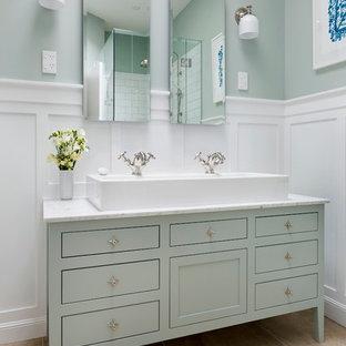 オークランドの中くらいのトラディショナルスタイルのおしゃれなマスターバスルーム (横長型シンク、家具調キャビネット、緑のキャビネット、大理石の洗面台、白いタイル、セラミックタイル、緑の壁、磁器タイルの床) の写真