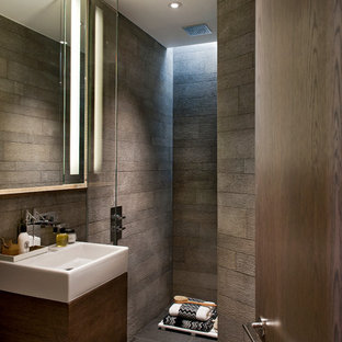 Réalisation d'une salle de bain design avec un placard à porte plane, des portes de placard en bois sombre, une douche ouverte, un carrelage marron et aucune cabine.