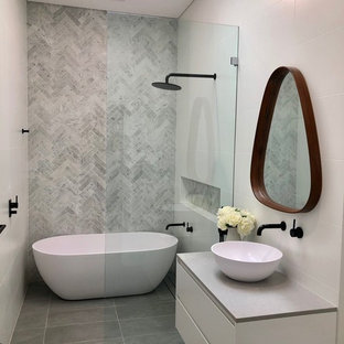 Photo of a contemporary wet room bathroom in Other with flat-panel cabinets, white cabinets, a freestanding tub, gray tile, a vessel sink, grey floor, an open shower and grey benchtops.