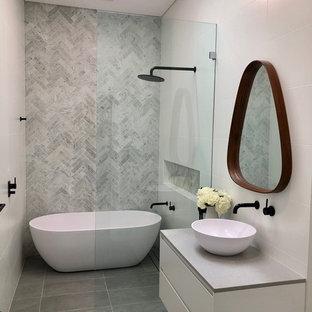 Esempio di una stanza da bagno design con ante lisce, ante bianche, vasca freestanding, zona vasca/doccia separata, piastrelle grigie, lavabo a bacinella, pavimento grigio, doccia aperta e top grigio