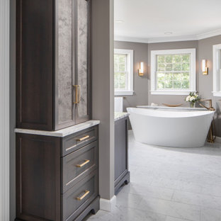 Inspiration for a huge transitional master gray tile and marble tile marble floor, gray floor and single-sink bathroom remodel in Other with recessed-panel cabinets, an undermount sink, granite countertops, a freestanding vanity, dark wood cabinets, a two-piece toilet, gray walls and white countertops