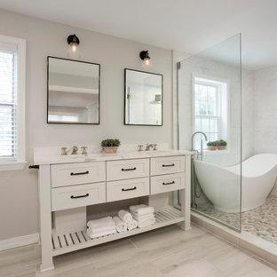 ボストンの広いトランジショナルスタイルのおしゃれなマスターバスルーム (家具調キャビネット、白いキャビネット、置き型浴槽、洗い場付きシャワー、一体型トイレ、白いタイル、磁器タイル、ベージュの壁、木目調タイルの床、アンダーカウンター洗面器、クオーツストーンの洗面台、ベージュの床、オープンシャワー、白い洗面カウンター、洗面台2つ、独立型洗面台) の写真