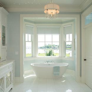 Foto de cuarto de baño clásico con puertas de armario blancas, bañera exenta, ducha empotrada, paredes azules y armarios tipo vitrina