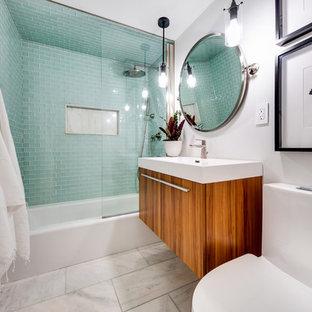 Inredning av ett modernt litet vit vitt en-suite badrum, med släta luckor, skåp i mellenmörkt trä, ett badkar i en alkov, en dusch/badkar-kombination, en toalettstol med hel cisternkåpa, grön kakel, glaskakel, grå väggar, marmorgolv, ett väggmonterat handfat, bänkskiva i kvarts, vitt golv och med dusch som är öppen