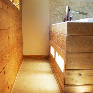 Idée de décoration pour une salle de bain principale design de taille moyenne avec un placard à porte plane, des portes de placard en bois brun, une baignoire posée, une douche d'angle, un carrelage beige, un carrelage de pierre, un mur beige, un sol en carrelage de céramique et un lavabo posé.