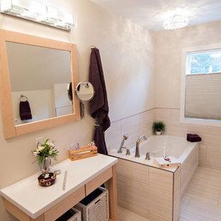 Immagine di una piccola stanza da bagno padronale chic con ante lisce, ante bianche, top in superficie solida, piastrelle in gres porcellanato, vasca ad angolo, WC a due pezzi, pareti beige, pavimento in vinile e lavabo sottopiano