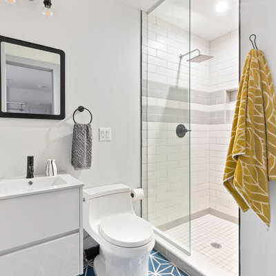 Inspiration for a mid-sized contemporary 3/4 gray tile, white tile and subway tile cement tile floor and blue floor bathroom remodel in New York with a one-piece toilet, gray walls, flat-panel cabinets, white cabinets, a console sink and white countertops