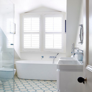 Traditional bathroom in London with a trough sink, a freestanding bath, an alcove shower, a two-piece toilet, multi-coloured tiles, white walls and ceramic flooring.