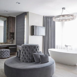 Example of a transitional master light wood floor freestanding bathtub design in Los Angeles with flat-panel cabinets and gray walls