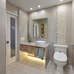 Modelo de cuarto de baño clásico renovado con armarios abiertos, baldosas y/o azulejos beige, baldosas y/o azulejos blancas y negros, suelo de baldosas tipo guijarro, paredes beige, lavabo sobreencimera y suelo gris