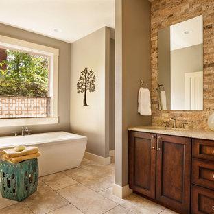 Ejemplo de cuarto de baño tradicional renovado con lavabo bajoencimera, armarios estilo shaker, puertas de armario de madera en tonos medios, bañera exenta y baldosas y/o azulejos de piedra