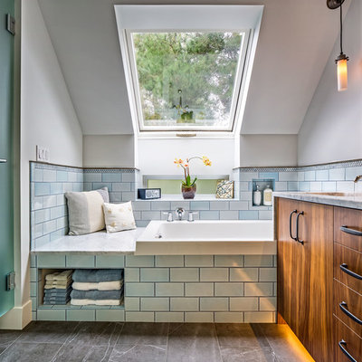 Example of a transitional blue tile and subway tile drop-in bathtub design in Seattle with flat-panel cabinets, dark wood cabinets and white walls