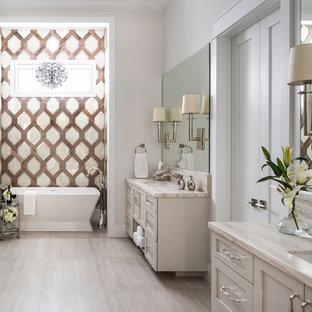 Esempio di una grande stanza da bagno padronale chic con ante in stile shaker, ante beige, vasca freestanding, pareti beige, lavabo sottopiano, top beige, doccia a filo pavimento, WC monopezzo, piastrelle beige, piastrelle a mosaico, pavimento in marmo, top in superficie solida, pavimento beige e porta doccia a battente
