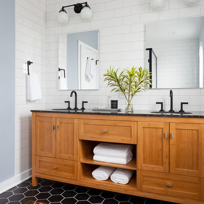 Example of a mid-sized transitional master black and white tile and ceramic tile porcelain tile and black floor corner shower design in Seattle with shaker cabinets, medium tone wood cabinets, gray walls, an undermount sink, quartz countertops and a one-piece toilet