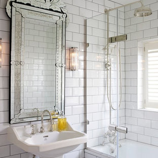 Traditional bathroom in London with a pedestal sink, a shower/bath combination, white tiles, metro tiles and white walls.