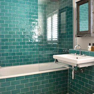 Modelo de cuarto de baño tradicional renovado con lavabo suspendido, bañera empotrada y baldosas y/o azulejos azules