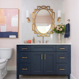 Cette photo montre une salle d'eau chic de taille moyenne avec des portes de placard bleues, un carrelage bleu, un carrelage en pâte de verre, un mur rose, un lavabo encastré, un plan de toilette en quartz, un plan de toilette blanc, un placard avec porte à panneau encastré, un WC séparé et un sol gris.