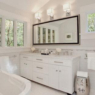 Ejemplo de cuarto de baño tradicional renovado con bañera exenta, lavabo bajoencimera, puertas de armario blancas, encimera de mármol, baldosas y/o azulejos blancos, baldosas y/o azulejos de cemento y armarios estilo shaker
